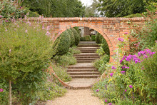 A Gravel Path Passes Through A Circular Archway In An Old Brick Wall, Which Leads On To Some Old Brick Steps In An English Country Garden