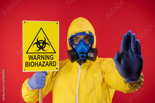 A man in a protective chemical mask and a protective yellow suit with a banner in his hand with the words biohazard shows a stop sign Fototapete