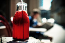 Close-Up Of Red Drink In Bottle On Table At Sidewalk Cafe