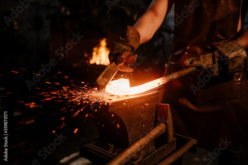 Brutal bearded peasant craftsman, banging on red hot metal on an anvil with a hammer in a dark workshop Canvas Print