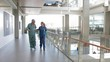 Male surgeon and female nurse walking and talking in hospital corridor