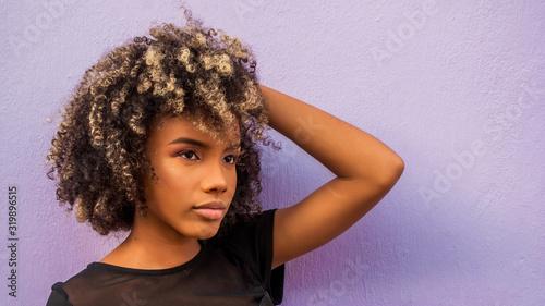 Mujer joven afrodecendiente cabello risado suelto con su braso levantado ocultan Wallpaper Mural