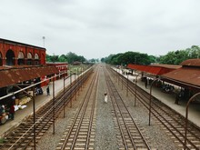 High Angle View Of Man Amidst Railroad Tracks At Station