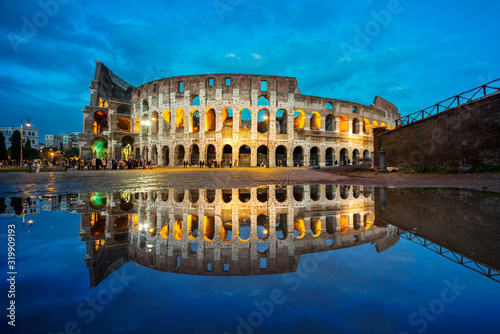 Obraz na plátně Roman Coliseum mirrored in the water in the blue hour