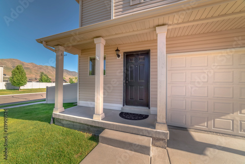Photo Home facade with concrete porch and front door adjacent to the garage door