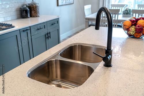 Obraz na plátně Stainless steel undermount double basin kitchen island sink with black faucet