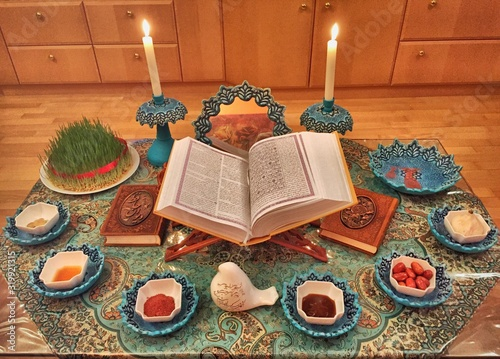 Obraz High Angle View Of Koran Amidst Foods And Lit Candles On Rug During Nowruz - fototapety do salonu