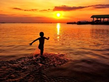 SILHOUETTE OF BOY PLAYING IN SEA