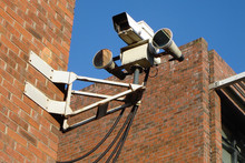 Low Angle View Of Security Camera Mounted On Brick Wall
