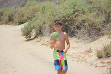 Shirtless Boy Holding Prickly Pear Cactus On Road