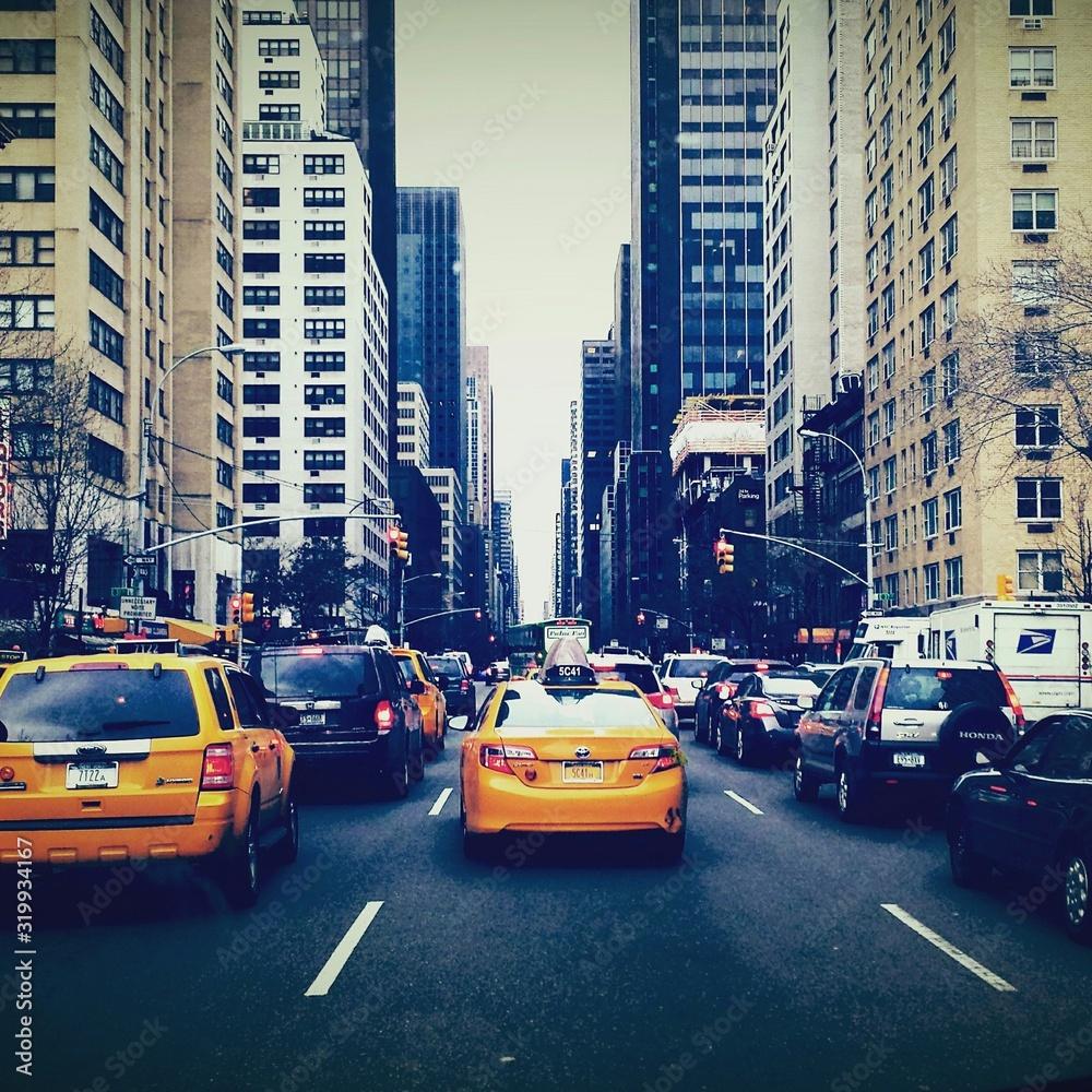 Fototapeta Rear View Of Vehicles On Road Along Buildings - obraz na płótnie