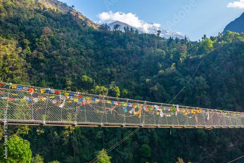 Fototapeta The suspension bridge named 'New Bridge' (278 m long) located nearly Jhinu Danda village, one of the famous village on the way to Annapurna Sanctuary of Nepal. obraz na płótnie