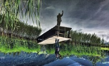Upside Down Image Of Man On Pier Reflecting In Lake