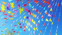 Low Angle View Of Colorful Bunting Flags Against Clear Blue Sky