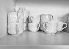 Close-Up Of Tea Cups In Shelf