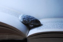 Close-Up Of Pebble On Open Book