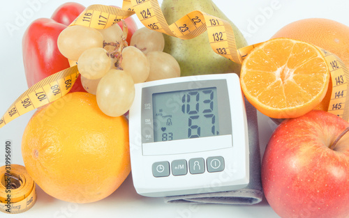 Fototapeta Vintage photo, Blood pressure monitor with result of measurement, fruits with vegetables and centimeter, healthy lifestyle obraz