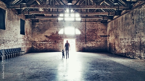 Photo Rear View Of Father With Son Walking In Old Building