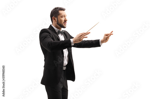 Vászonkép Male conductor in a suit conducting with a baton and gesturing with hand