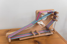 A Small, Tabletop, Inkle Loom On Which A Band, Or Strap, Is In The Process Of Being Woven.