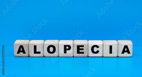concept word alopecia on cubes on a blue background Canvas Print