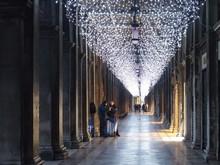 People Walking On Corridor Below Hanging Lights