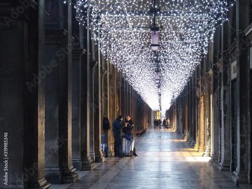 Carta da parati People walking on corridor below hanging lights