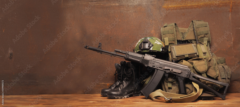 Fototapeta Concept - service, security, Armed Forces, Private military company, navy, mercenary. Weapons, helmet, cleats, body armor on a rustic background.