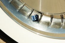 Close-Up Of Dice On Whitewall Tire Of Car
