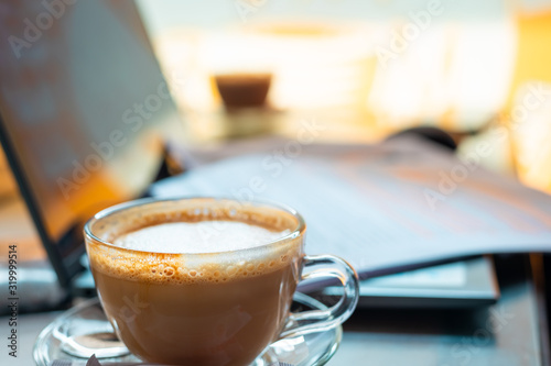 A cup of cappuccino with paperworks resting on a laptop in the backdrop Canvas Print