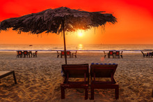 Sunset At Tropical Beach With Lounge Chairs And Beach Umbrellas In GOA, India