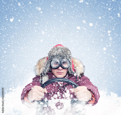 obraz dibond Driving man in red winter clothes and stylish goggles holds a steering wheel in his hands, around the snow. Front view