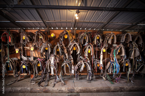 Leather Saddles Hanging Against Wall In Barn Poster Mural XXL