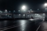 Foggy misty night road and overhead pedestrian bridge illuminated by street lights