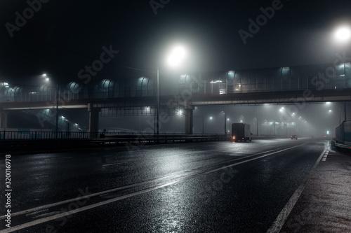 Foggy misty night road and overhead pedestrian bridge illuminated by street lights