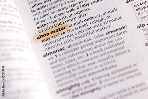 Photo The word or phrase Alma Mater in a dictionary.