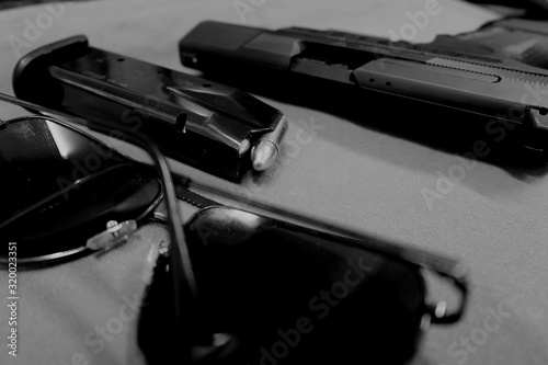Fotografie, Obraz Close-Up Of Sunglasses With Handgun And Magazine