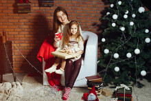 Two Cute Sisters Sitting Near Christmas Tree. Cute Girls Sitting On A White Chair