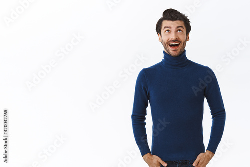 Enthusiastic lucky good-looking businessman in blue high neck sweater, looking u Wallpaper Mural