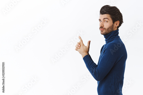 Fotografia Sassy handsome man in stylish high neck sweater, standing in profile turn at cam