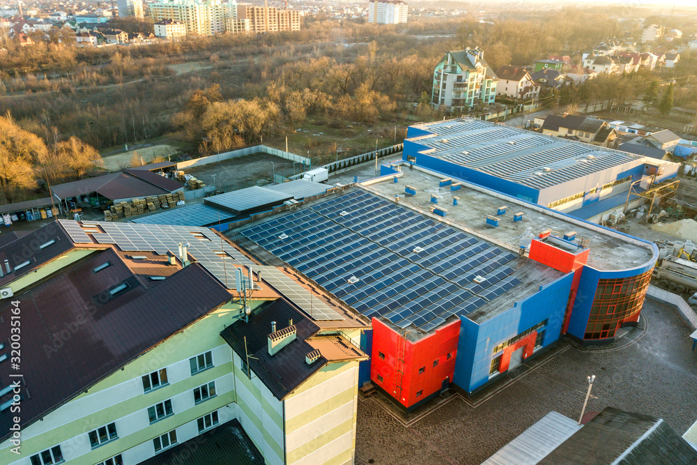 Fototapeta Aerial view of many photo voltaic solar panels mounted of industrial building roof.