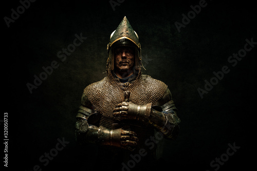 Canvas Print Portrait of a knight in armor holding his sword in his hands