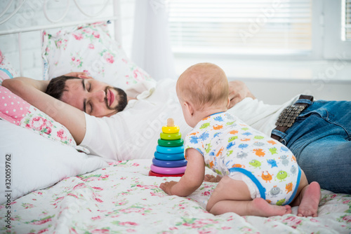 Photo Little six-month-old baby plays with toys on the bed against the background of a tired, sleeping young father