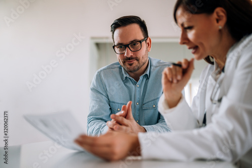 Close-up image of smiling man listening to a female healthcare worker, portrait Fototapeta