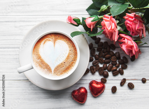 Fototapeta A cup of coffee with heart pattern on a table obraz