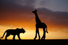 Close-Up Of Silhouette Tiger And Giraffe Toys Against Orange Sky