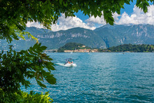 Picturesque View Of The Blue Waters Of Lake Como With Floating Motor Boats, Overhanging Branches With Green Leaves In The Foreground, The Village Of Bellagio And An Impressive Mountain In The Horizon.