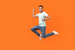 canvas print picture - Full length portrait of positive inspired brunette man with beard in sneakers, denim outfit jumping in air or running quickly fast. indoor studio shot isolated on orange background, empty copy space