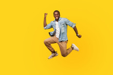 Full Length Portrait Of Joyous Ecstatic Man In Denim Shirt Jumping For Joy Or Flying With Raised Hand, Gesturing Yes I Did It, Celebrating Success. Indoor Studio Shot Isolated On Yellow Background