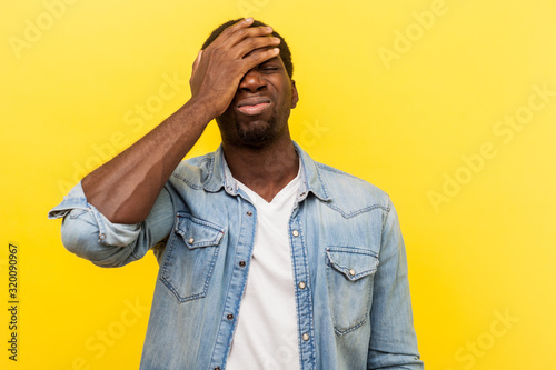 Facepalm, I forgot. Portrait of regretful man in denim casual shirt holding hand on face, feeling sorrow and desperation about failure, his fault. indoor studio shot isolated on yellow background